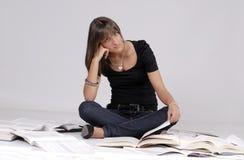 Allievo femminile che si siede fra i suoi libri Immagine Stock