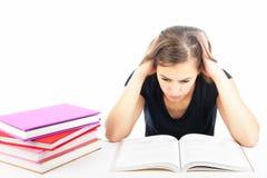 Allievo femminile che studia ad uno scrittorio con i libri Fotografia Stock