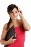 Allievo femminile che tiene un dispositivo di piegatura e una matita Immagini Stock Libere da Diritti