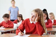Allievo femminile che trova l'esame della scuola difficile Fotografia Stock Libera da Diritti
