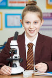 Allievo femminile che utilizza microscopio nella lezione di scienza Immagini Stock Libere da Diritti