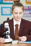 Allievo femminile che utilizza microscopio nella lezione di scienza Fotografie Stock Libere da Diritti