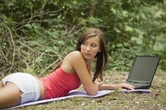 Allievo femminile con il computer portatile in foresta Fotografia Stock
