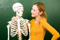 Allievo femminile con lo scheletro Immagini Stock