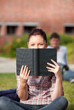 Allievo femminile concentrato che legge un libro esterno Fotografia Stock