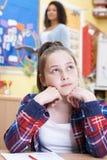Allievo femminile della scuola elementare che fantastica nella classe Fotografie Stock