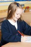 Allievo femminile della scuola elementare che lavora allo scrittorio Immagini Stock