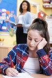 Allievo femminile della scuola elementare che lotta nella classe Immagini Stock Libere da Diritti