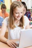 Allievo femminile della scuola elementare che utilizza computer portatile nella classe del computer Immagine Stock Libera da Diritti