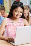 Allievo femminile della scuola elementare che utilizza computer portatile nella classe del computer Immagini Stock Libere da Diritti