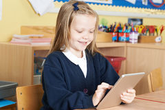 Allievo femminile della scuola elementare che utilizza la compressa di Digital nella classe Fotografia Stock