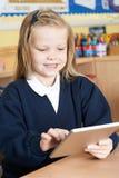 Allievo femminile della scuola elementare che utilizza la compressa di Digital nella classe Fotografia Stock Libera da Diritti