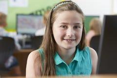 Allievo femminile della scuola elementare nella classe del computer Immagini Stock