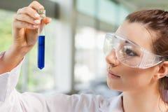 Allievo femminile di scienza che esamina una provetta Fotografie Stock