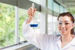 Allievo femminile di scienza che tiene un liquido blu Immagini Stock