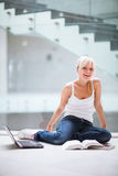 Allievo femminile grazioso con il computer portatile ed i libri Fotografia Stock