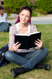 Allievo femminile intelligente che legge un libro sull'erba Fotografia Stock