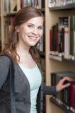 Allievo femminile in libreria Immagine Stock