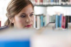 Allievo femminile in libreria Immagini Stock Libere da Diritti