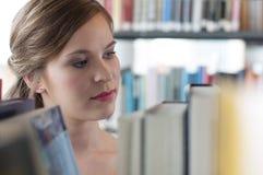 Allievo femminile in libreria Fotografie Stock Libere da Diritti