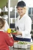 Allievo femminile nel self-service di scuola che è servito pranzo dalla La della cena Fotografia Stock