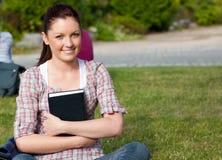 Allievo femminile positivo che tiene un libro in una sosta Fotografia Stock