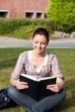 Allievo femminile Relaxed che legge un libro all'aperto Immagine Stock Libera da Diritti