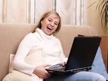 Allievo femminile sorridente sul sofà. Fotografie Stock Libere da Diritti