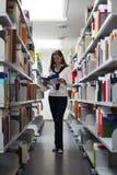 Allievo fra la lettura degli scaffali per libri Fotografia Stock