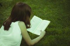 allievo Giovane bella ragazza che legge un libro esterno Fotografie Stock