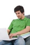 Allievo - giovane con il computer portatile sul sacchetto di fagiolo Immagini Stock Libere da Diritti