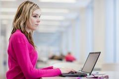Allievo grazioso e femminile con il computer portatile e libri Immagini Stock Libere da Diritti