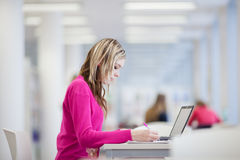 Allievo grazioso e femminile con il computer portatile e libri Fotografie Stock