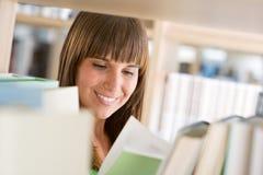 Allievo in libreria - la donna allegra ha letto il libro Immagine Stock