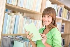 Allievo in libreria - la donna allegra sceglie il libro Fotografie Stock Libere da Diritti