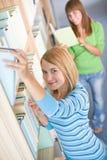 Allievo in libreria - la donna due sceglie il libro Immagine Stock