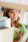 Allievo in libreria - la donna fa una pausa lo scaffale per libri Immagine Stock