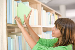 Allievo in libreria - la donna felice sceglie il libro Immagine Stock