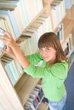 Allievo in libreria - ricerca felice della donna del libro Fotografie Stock Libere da Diritti