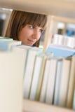 Allievo in libreria - studio felice della donna dal libro Immagini Stock