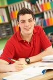 Allievo maschio adolescente nel funzionamento nell'aula Immagini Stock