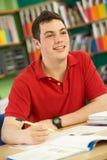 Allievo maschio adolescente nel funzionamento nell'aula Fotografie Stock Libere da Diritti