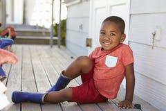 Allievo maschio alla scuola di Montessori che mette su Wellington Boots Fotografia Stock