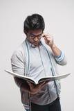 Allievo maschio asiatico che legge un libro Immagini Stock