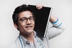 Allievo maschio asiatico che tiene un libro sulla spalla Fotografia Stock Libera da Diritti