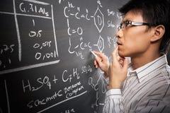 Allievo maschio che lavora all'equazione Fotografia Stock Libera da Diritti
