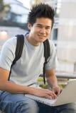Allievo maschio che per mezzo del computer portatile all'esterno Fotografia Stock