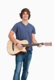 Allievo maschio che propone mentre tenendo una chitarra Fotografia Stock