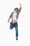 Allievo maschio che propone saltando con un braccio alzato Fotografia Stock Libera da Diritti