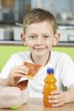 Allievo maschio che si siede alla Tabella nel cibo del self-service di scuola non sano Immagine Stock